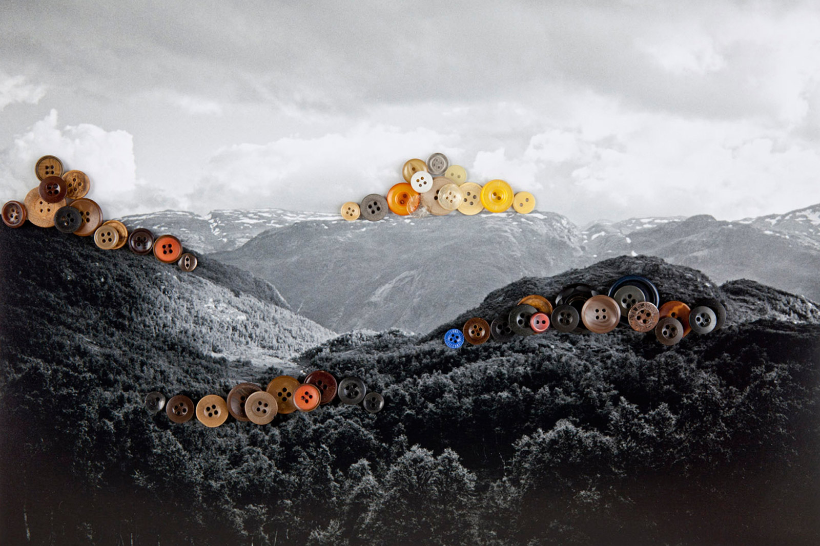 A photograph of a photograph of the mountains in Norway with colorful buttons laid on top.