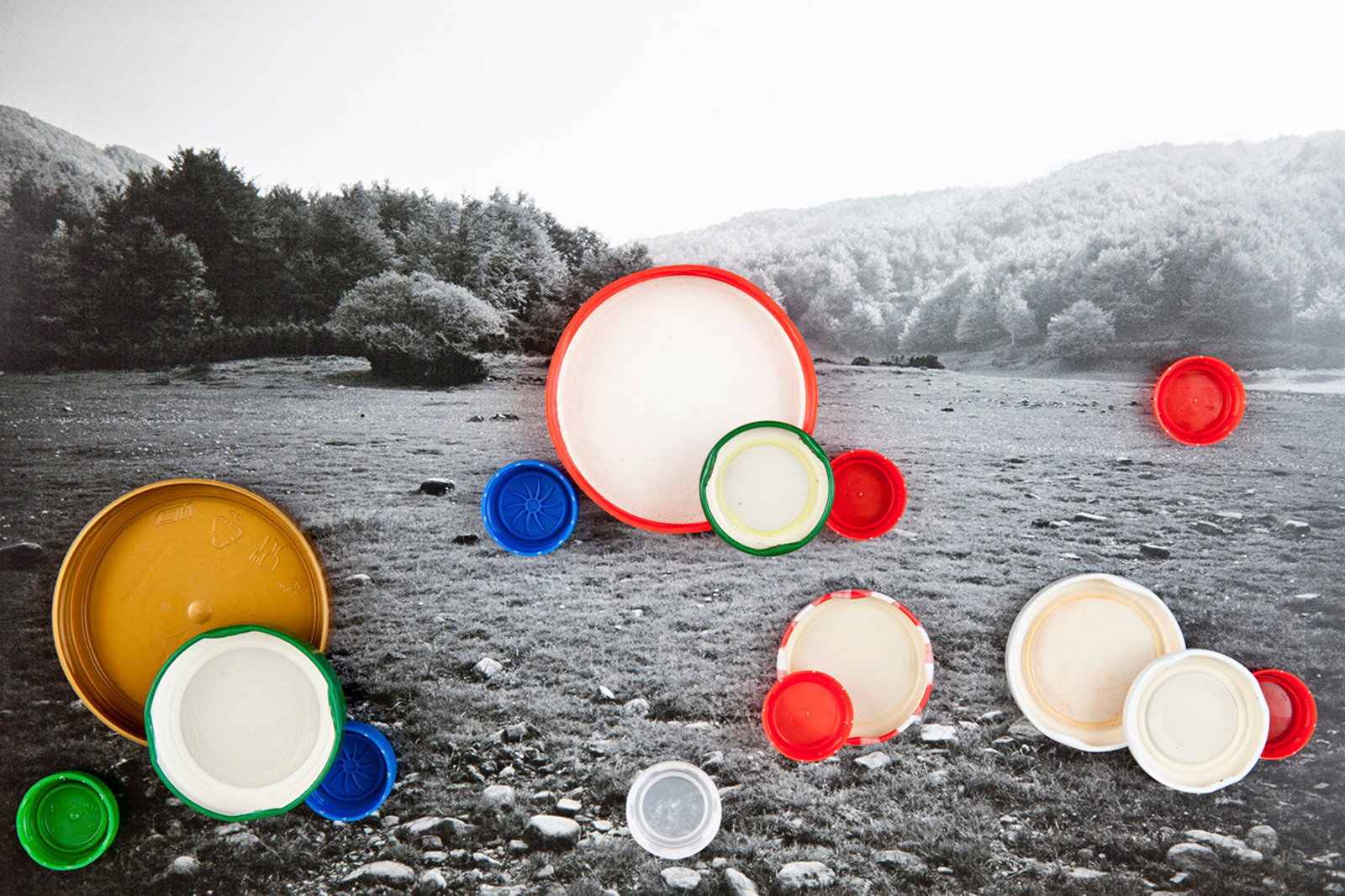 A photograph of a black and white photograph of the countryside in Italy with colorful bottle tops laid on top.