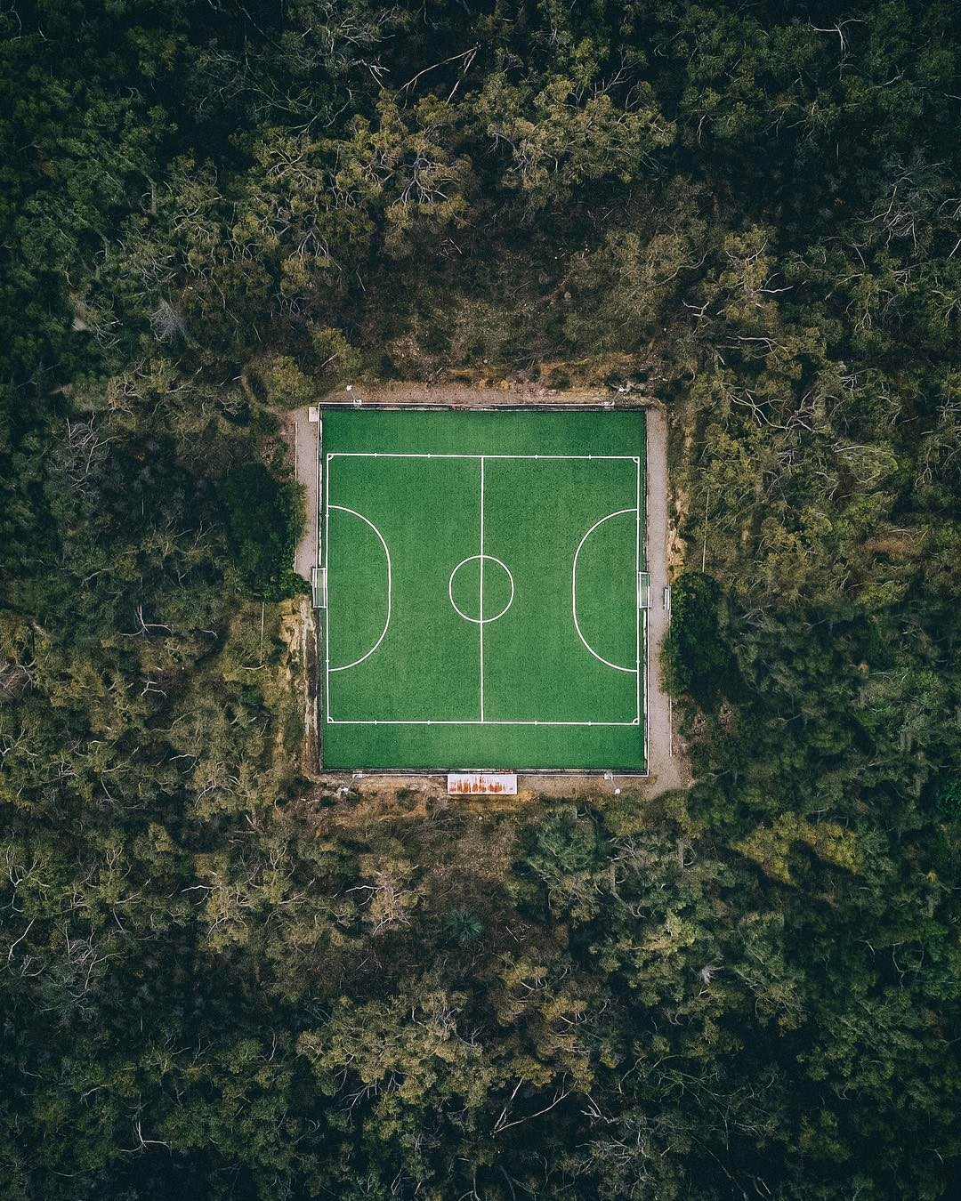 A hockey court in Adelaide, Australia surrounded by forest on all sides, taken with a DJi Maverick drone.