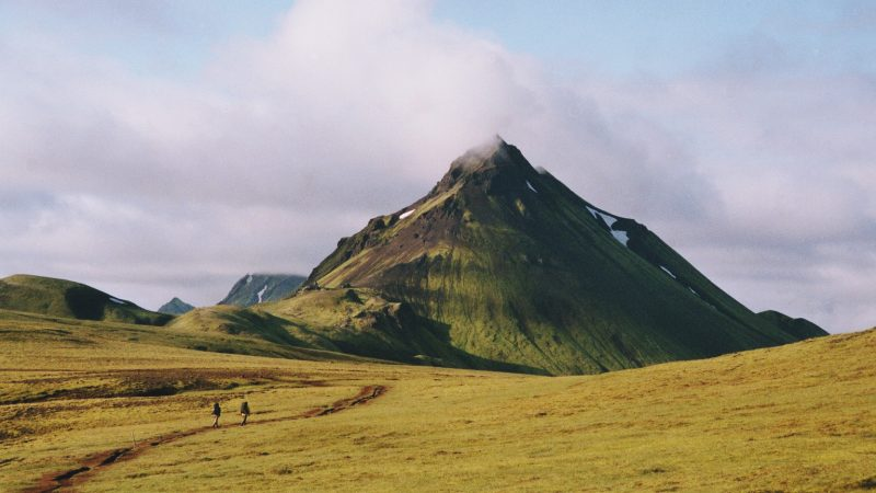 Two people walking in the very green, very large mountains of Iceland