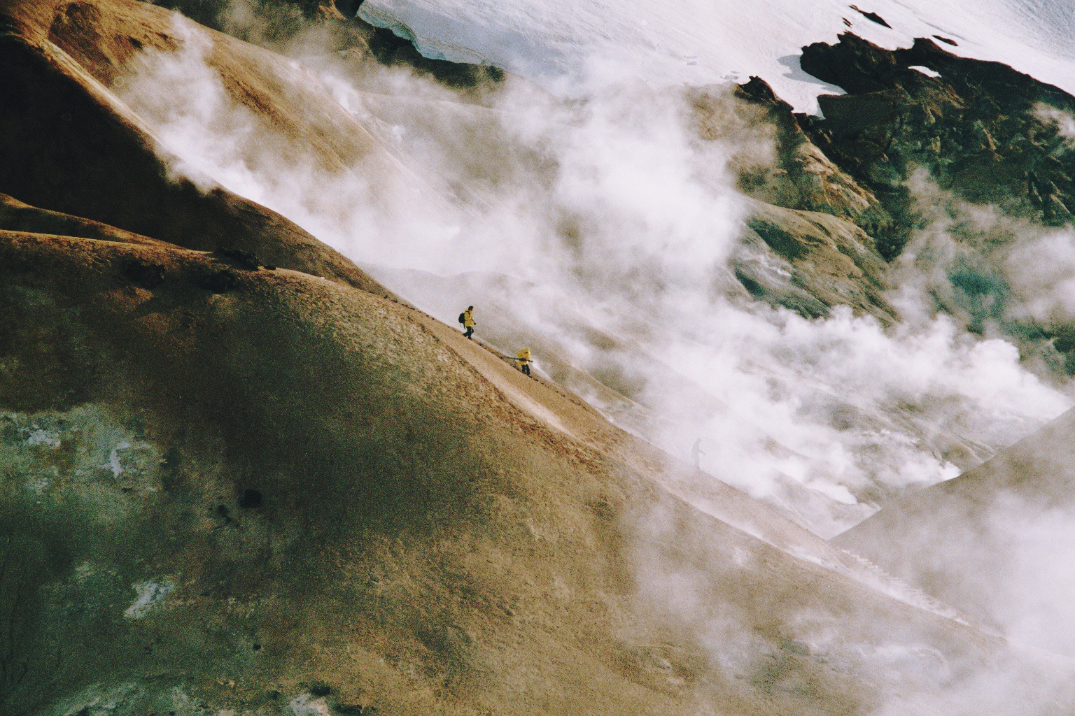 Two people walking in the misty mountains of Iceland