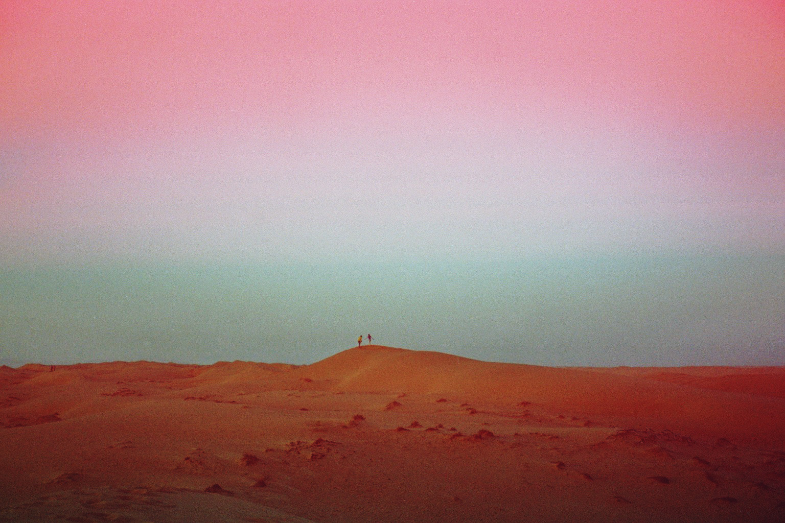 Two people walking in the distance of a desert in Oman.