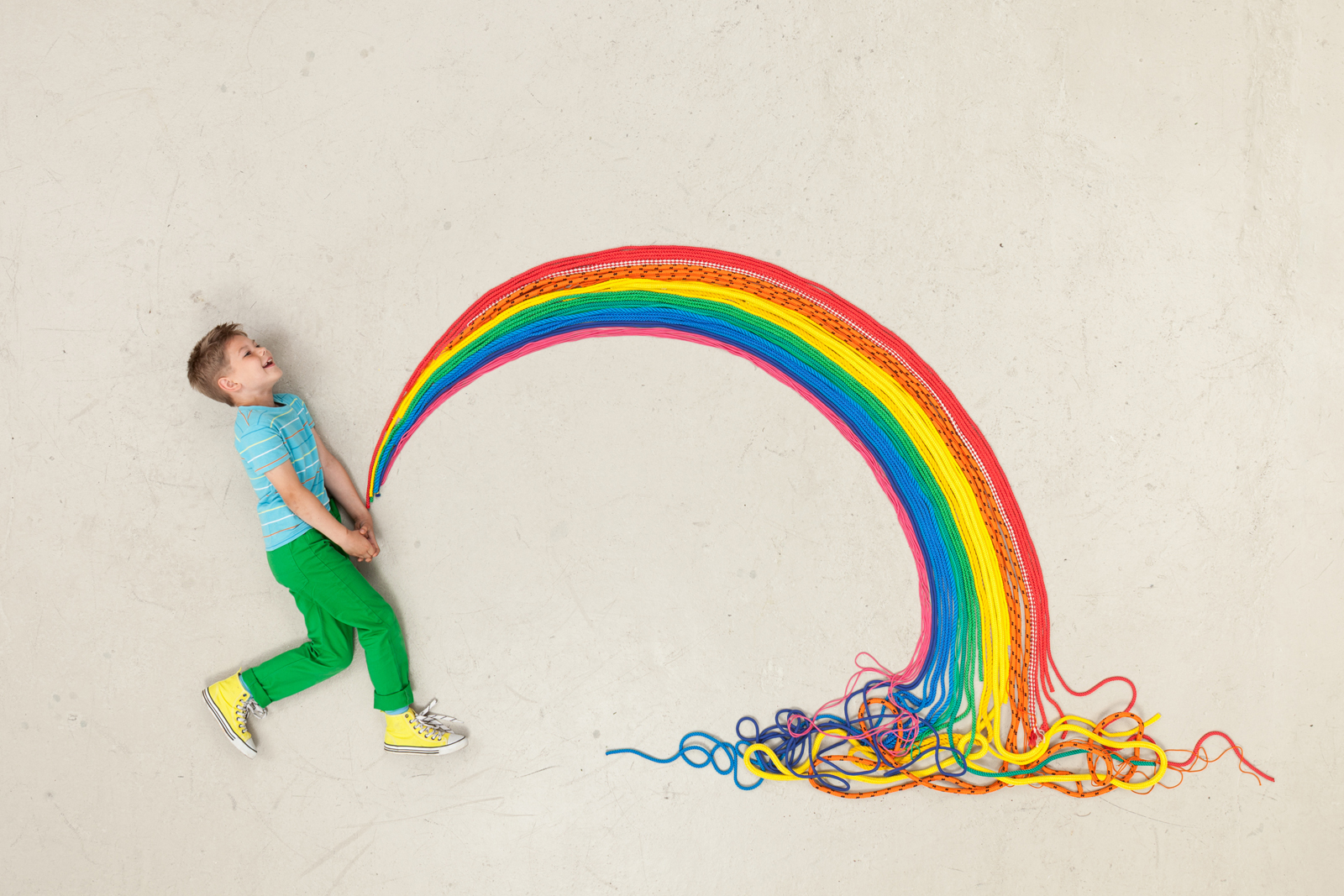 A photograph of a boy who looks like he's peeing a rainbow of string.
