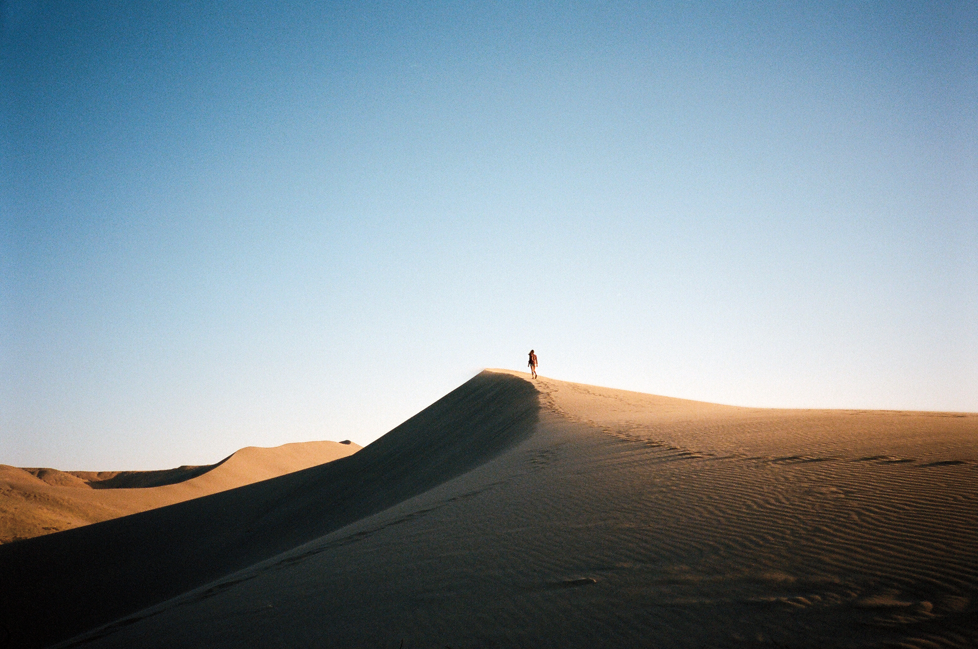 Desert sand dunes with person walking through them