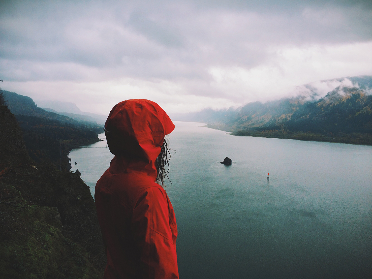 Girl in Red Jacket Looking Over Mountains and Water